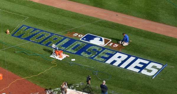 A member of the grounds crew paints a