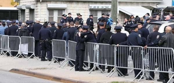 Police officers and other mourners file into the