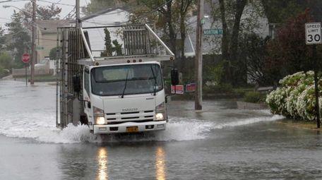 A work truck plows through tire-deep water on