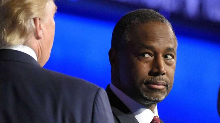 Ben Carson watches as Donald Trump takes the