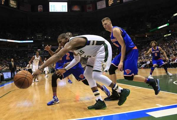Milwaukee Bucks center Greg Monroe, front, reaches for