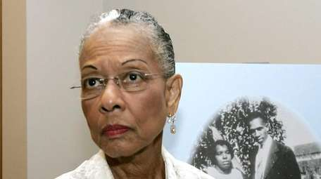 Juanita Evangeline Moore stands by a picture of