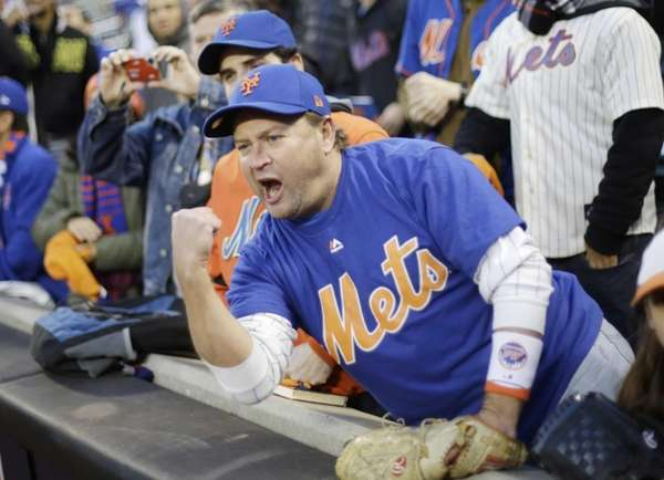 A New York Mets fan cheers before Game