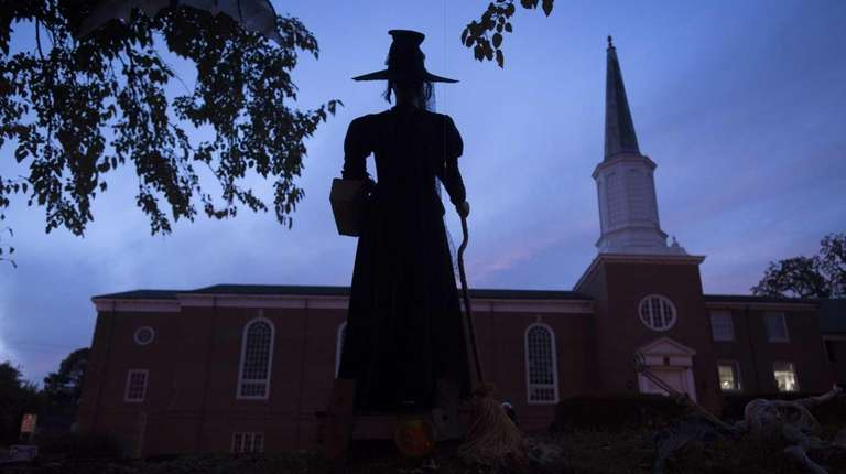 The silhouette of a witch figurine is seen