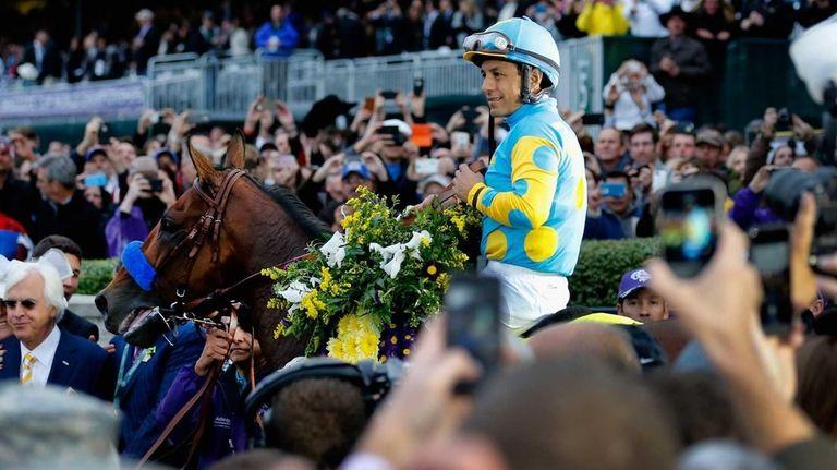 Jockey Victor Espinoza celebrates in the winner's circle