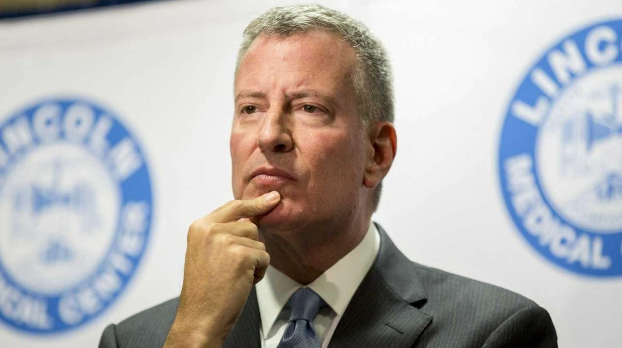 Mayor Bill de Blasio listens to a reporter's