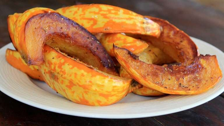 Gold acorn squash is cut in wedges and