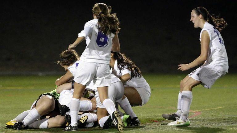 The Islip girls varsity soccer team mob their