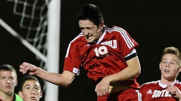 Noah Mina of Southold heads the ball in