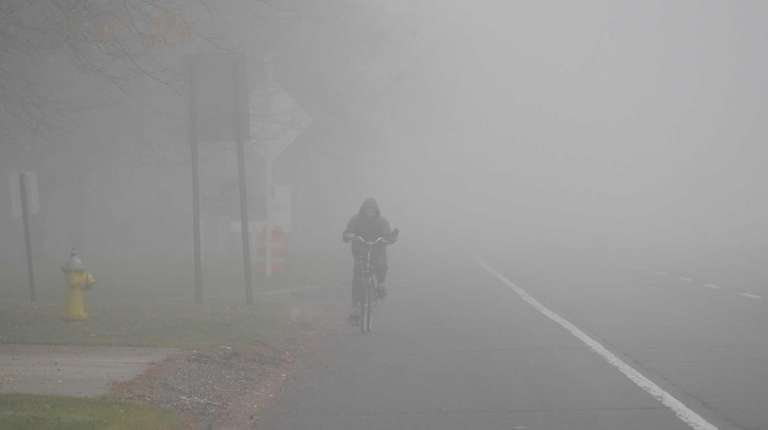 A man rides his bicycle through thick fog