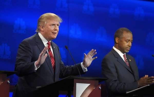 Donald Trump, left, speaks as Ben Carson looks