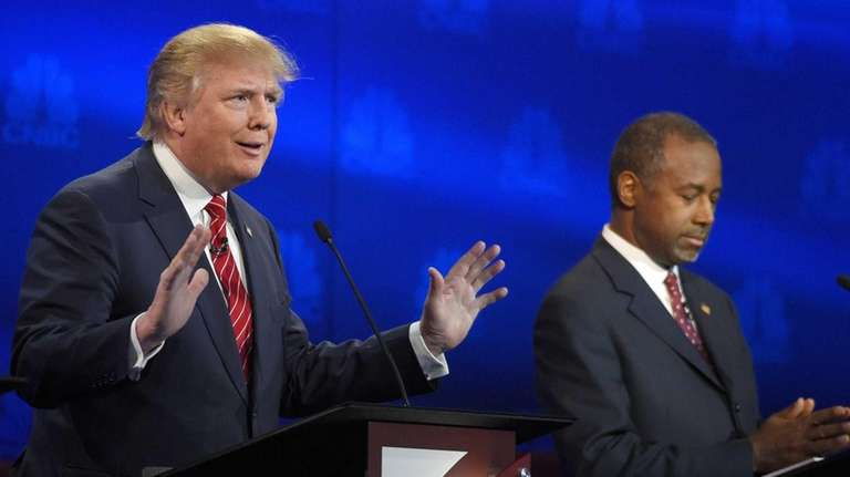 Donald Trump, left, speaks as Ben Carson looks