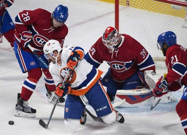 The New York Islanders' Cal Clutterbuck, center, moves
