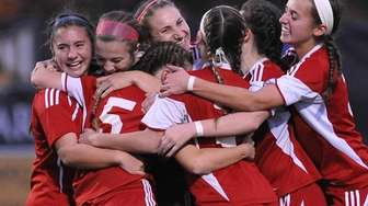 Center Moriches teammates celebrate after a goal by