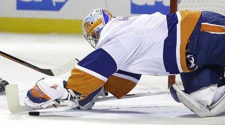 New York Islanders' Brian Strait watches as as