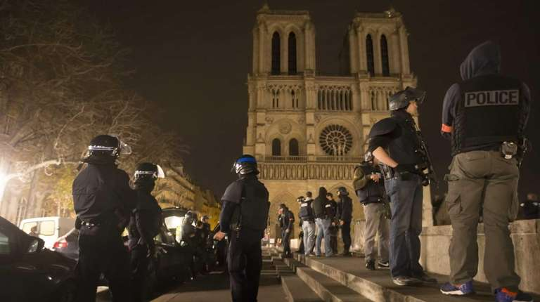 Armed police officers patrol on foot around Notre