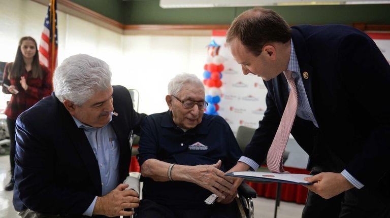 World War II veteran Ben Gebbia, center, receives