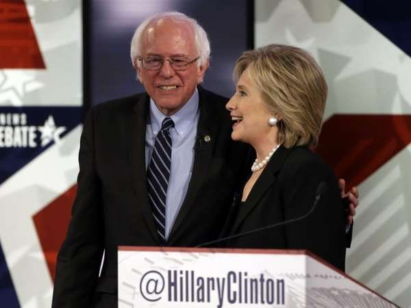 Hillary Clinton talks to Sen. Bernie Sanders after