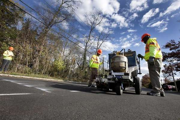 Contractors add striping to a newly paved stretch