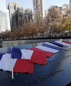 French flags rest on the engraved names at