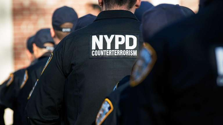 Police officers await the announcement, by New York