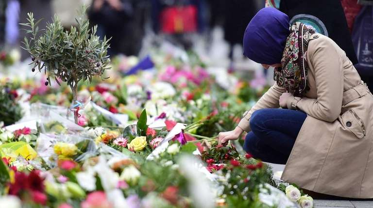 A Muslim woman lights a candle at a
