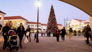 Shoppers walk through the central plaza at the