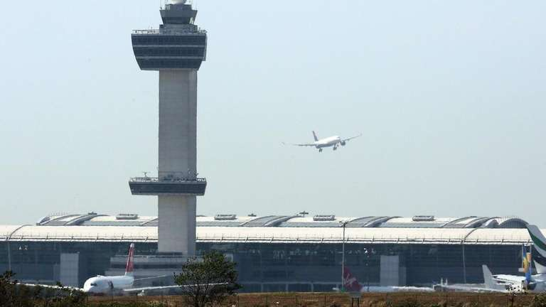 An aircraft flies past the control tower as