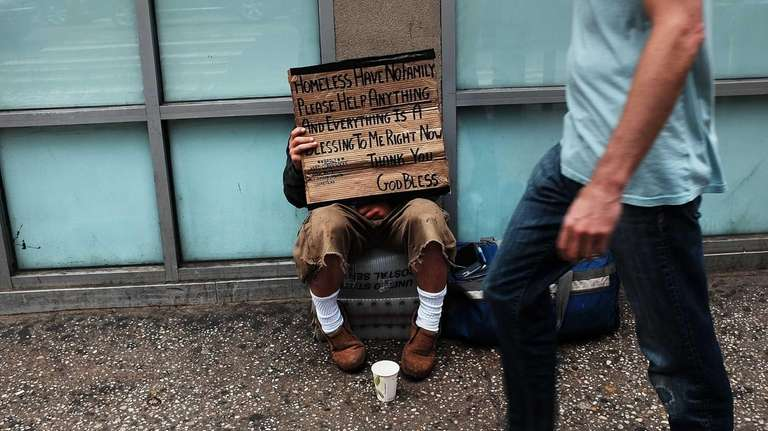 A homeless man panhandles along Eighth Avenue in