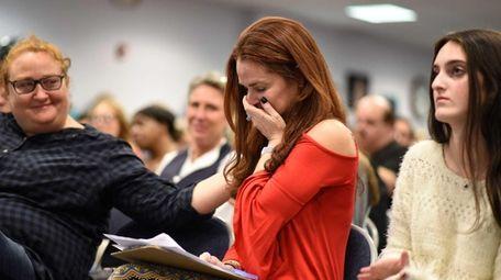 Parent Jennifer Boudin, center, of Melville, is brought