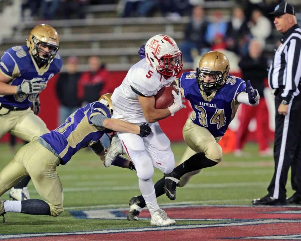East Islip's Justin Taveras #5 fights for yardage