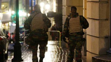 Belgian police officers walk along a road in