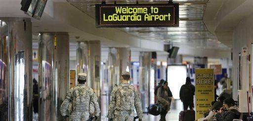 Security personnel walk through a terminal at LaGuardia