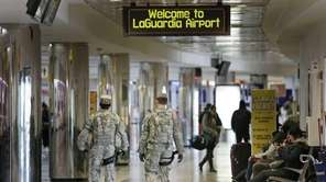 Security personnel walk through a terminal at LaGuardia