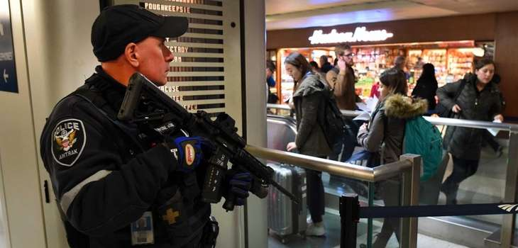 An Amtrak police officer watches passengers as they