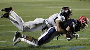 Newfield cornerback Elijah Riley (8) takes down MacArthur