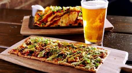 A flatbread topped with barbecued duck, poblano chilies,