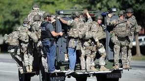 A SWAT vehicle carries police officers near the