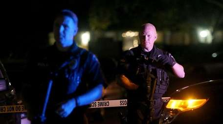 Redlands police officers stand guard as they investigate