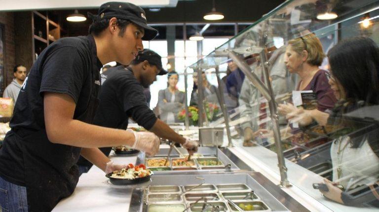 Countermen serve customers at Just Falafel in Carle