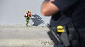 A San Bernardino police officer stands by flowers