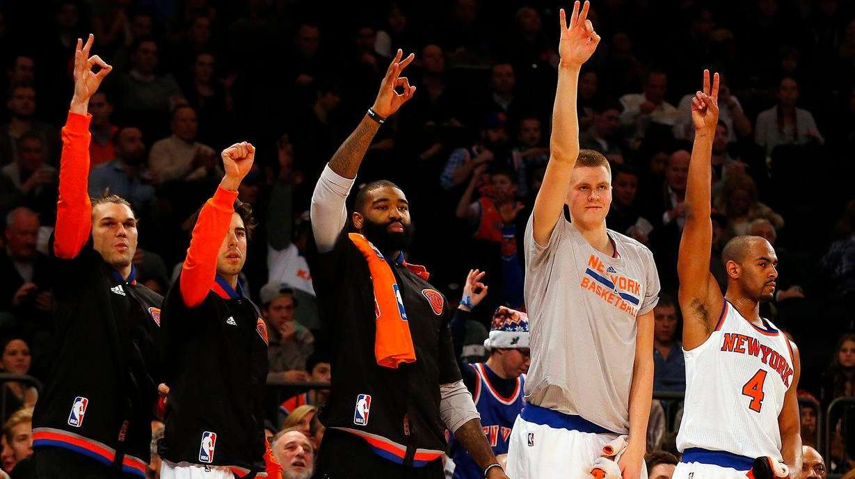 The New York Knicks bench celebrates a three