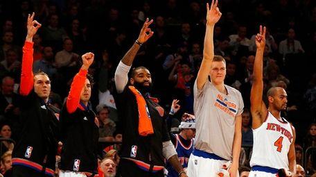 The New York Knicks bench celebrates a three