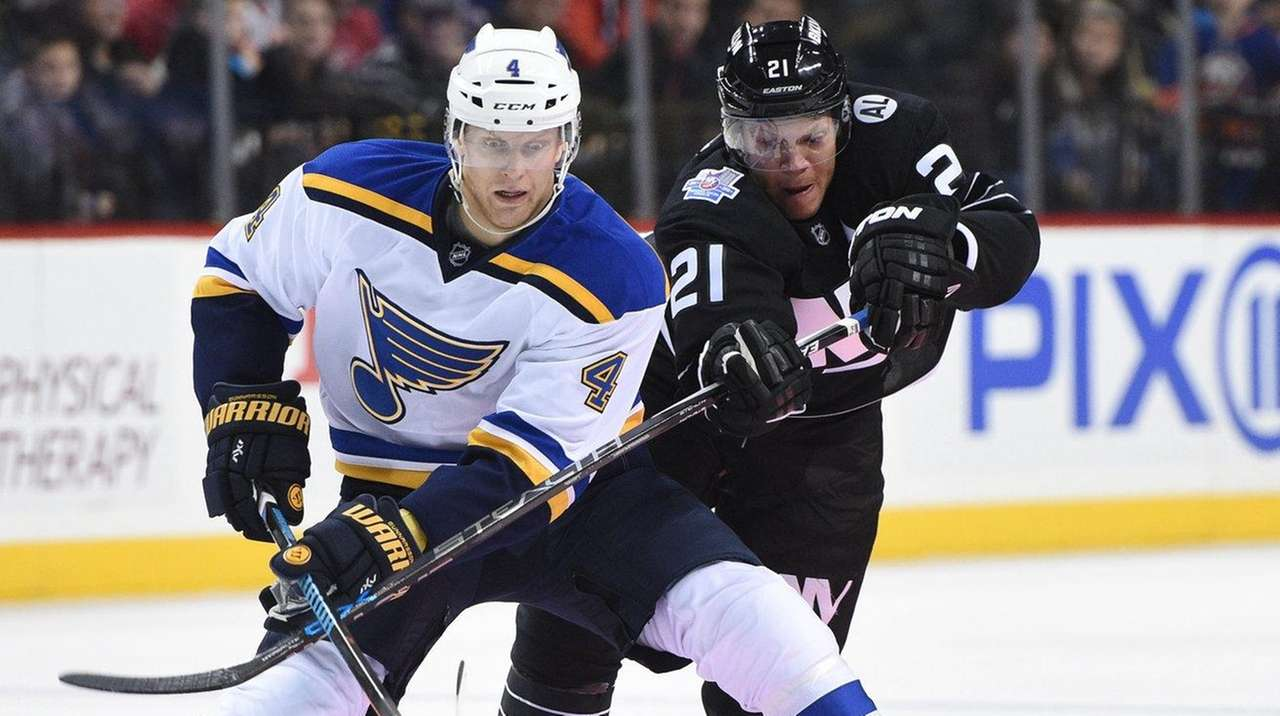 Islanders right wing Kyle Okposo, right, battles Blues