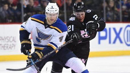 Islanders right wing Kyle Okposo, right, battles Blues