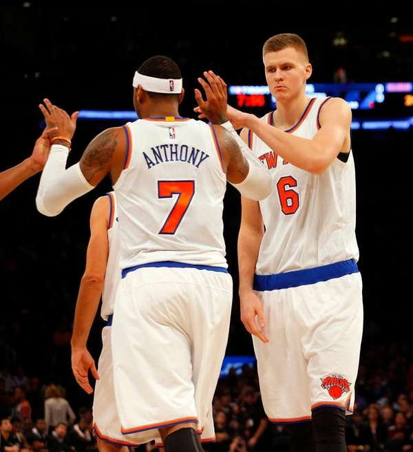 Kristaps Porzingis and Carmelo Anthony celebrate after a