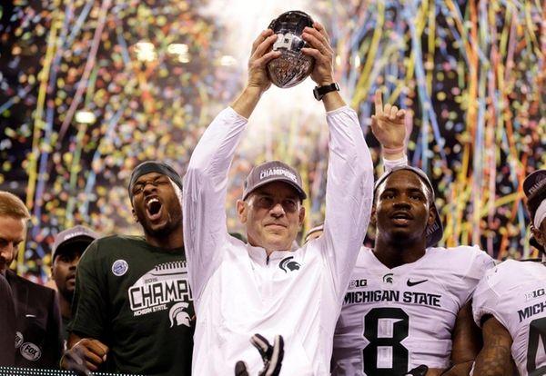 Michigan State coach Mark Dantonio holds the trophy
