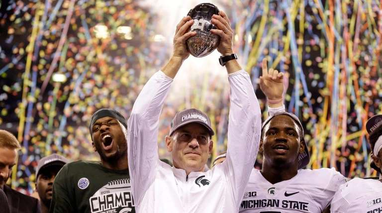 Michigan State coach Mark Dantonio holds the trophy
