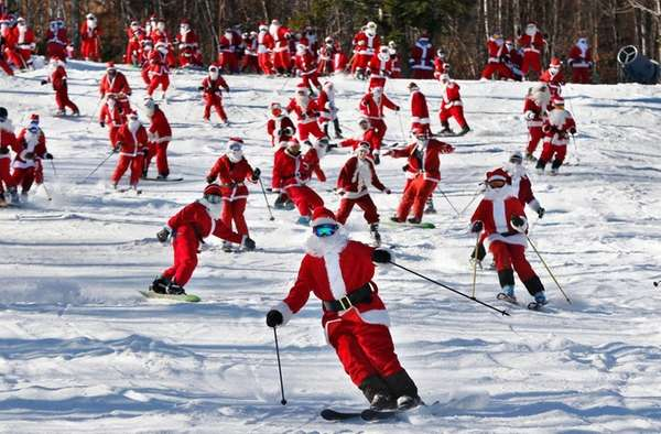 Skiers and snowboarders dressed as Santa take a