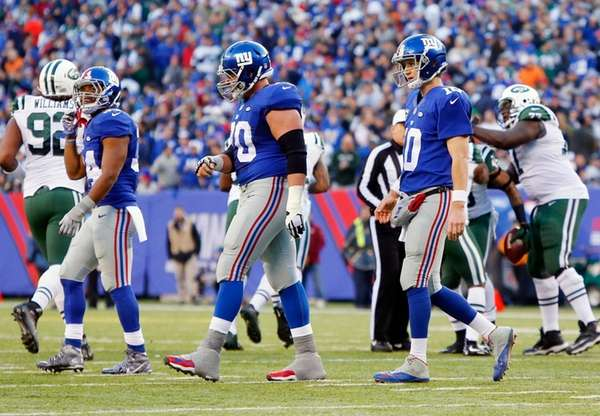 Eli Manning, right, walks off the field with